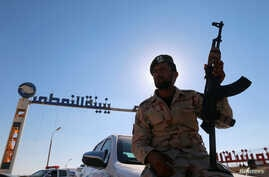 A member of Libyan forces loyal to eastern commander Khalifa Haftar holds a weapon as he sits on a car in front of the gate at Zueitina oil terminal in Zueitina, west of Benghazi, Libya, Sept. 14, 2016.