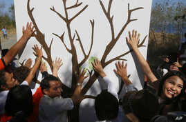 """Environmentalists make symbolic hand prints on a tree wall prior to a coastal clean up to mark World Earth Day Friday, April 22, 2016 at a bird sanctuary known as """"Freedom Island"""" in suburban Las Pians city, south of Manila, Philippines."""