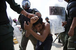 Policemen detain a man during clashes with garment workers in Phnom Penh, Nov. 12, 2013.