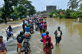 People move past a flooded road in Thrissur, in the southern Indian state of Kerala, Aug. 17, 2018.