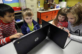FILE - Second-grader Josh Mercado, left, helps kindergartner Erik Hodges, as second-grader Annabelle Davis, right, helps kindergartner Kaidyance Harris, on programming during their weekly computer science lesson at Marshall Elementary School in Marys