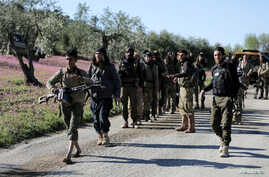 Turkish-backed Free Syrian Army fighters walk together after advancing north of Afrin, Syria, March 17, 2018.