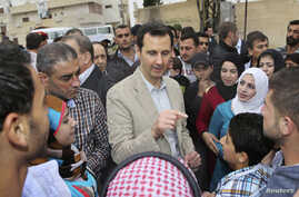 Syrian President Bashar al-Assad (C) chats with people during his visit to Ein al-Tinah village, northeast of Damascus April 20, 2014, in this handout photograph released by Syria's national news agency SANA. Apart from Ein al-Tinah, Assad on Sunday