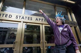 FILE - In this June 19, 2018, file photo, protester Ann Marie Stenberg yells outside the Immigration and Customs Enforcementoffice in San Francisco. A U.S. judge in California struck down an immigration law, Oct. 5, 2018, that the Trump administrati
