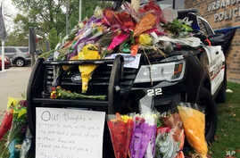 """A memorial grows outside the police department in Urbandale, Iowa, Nov. 2, 2016, following the shooting deaths of two area police officers. Urbandale police Officer Justin Martin and Des Moines police Sgt. Anthony """"Tony"""" Beminio were shot to death e"""