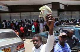 FILE - A man holds old notes in front of people queueing for cash at a local bank during a demonstration against the new 'bond notes' that came into circulation this week in an attempt to ease chronic cash shortages, in the capital Harare, Zimbabwe,