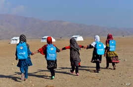Afghan schoolgirls hold hands and walk towards their tent classrooms on the outskirts of Jalalabad, capital of Nangarhar province, Afghanistan, Dec. 13, 2016.