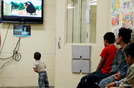 FILE - A detained immigrant child watches a cartoon with other young detained immigrants at a U.S Customs and Border patrol immigration detainee processing facility in Tucson, Arizona,  June 28, 2018.
