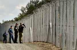 FILE - A police officer, second right, and border guard, right, of Poland patrol with Hungarian policemen along the temporary border fence on the Hungarian-Serbian border near Roszke, 180 kms southeast of Budapest, Hungary, Oct. 13, 2016.