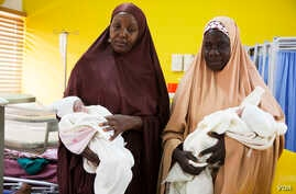 Hajia Muhammed's relatives carry her healthy twin boys. She delivered with a C-section because one of the twins was in a breeched position in Kaduna, Nigeria. (Photo: Chika Oduah for VOA)