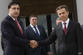 Georgian President Mikhail Saakashvili, left, and Bidzina Ivanishvili, right, the likely new prime minister, shake hands before their meeting at the Presidential Palace in Tbilisi, October 9, 2012.