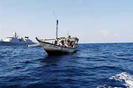 A handout picture received from The Netherlands Ministry of Defence shows a boat containing alleged Somali pirates being apprehended by Netherlands warship Evertsen acting as part of EU counter piracy operations at sea some 150 nautical miles off the