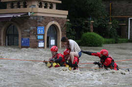 Firefighters rescue a stranded woman on a flooded street following heavy rainfall in Chengdu, Sichuan province, China, July 11, 2018.