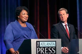 Democratic gubernatorial candidate for Georgia Stacey Abrams, left, speaks as her Republican opponent Secretary of State Brian Kemp looks on during a debate in Atlanta, Oct. 23, 2018.