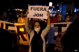 "A woman holds a sign with a message that reads in Spanish ""Get out JOH"" during a protest against Honduran President Juan Orlando Hernandez, in Tegucigalpa, Honduras, Jan. 26, 2018. Hernandez was awarded the electoral win last month despite the disput"