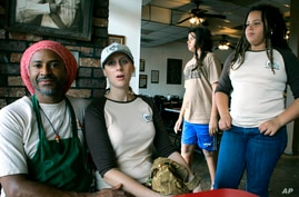 FILE - Al Stamps listens as his wife, Kim, speaks about her home schooling their chidren, son Alkebu-lan, 12, background, and daughter Abyssinia, 10, right, at Cool Al's, a popular restaurant in Jackson, Mississippi, April 3, 2007.