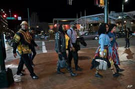 FILE - In this Feb. 15, 2018, file photo, Emanuel Lawton, left, and his family dressed in Wakanda-inspired attire arrive to see Black Panther in Silver Spring, Md.