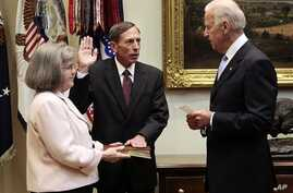 Holly Knowlton Petraeus holding the family bible as her husband David Petraeus is sworn in by Vice President Joe Biden as CIA Director, in the Roosevelt Room of the White House in Washington, September 6, 2011.