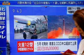 A woman walks past a TV screen broadcasting news of North Korea's missile launch, in Tokyo, Aug. 29, 2017. North Korea fired a ballistic missile from its capital Pyongyang that flew over Japan before plunging into the northern Pacific Ocean.