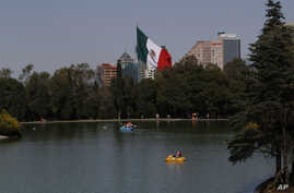 FILE - Paddle boaters make their way around a lake in the Chapultepec Park in Mexico City, Nov. 19, 2012. Chapultepec is a park divided between shady stretches of forest and more-developed plazas, fountains and sculpture gardens.