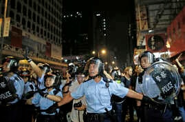 Riot police advance on a pro-democracy protest encampment in the Mong Kok district of Hong Kong early, Oct. 19, 2014.