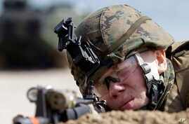 A U.S. Marine from the 31st Marine Expeditionary Unit aims his machine gun during the joint U.S.-South Korean military exercises, Foal Eagle, in Pohang, south of Seoul, South Korea, March 29, 2012.