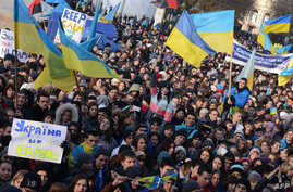 Students hold placards and flags as thousands rally in the western Ukrainian city of Lviv during a rally of pro-European supporters, Nov. 27, 2013.