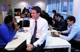 Former French Prime Minister Manuel Valls, now candidate for the socialist party primary election, smiles during the inauguration of his campaign headquarters, Dec. 14, 2016, in Paris. French officials are working to secure the election from cyberatt