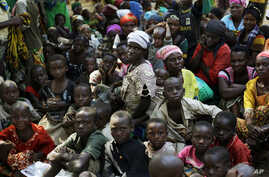 FILE - Refugees who fled Burundi's violence and political tensions wait to board a U.N. ship, at Kagunga on Lake Tanganyika, Tanzania, to be taken to the port city of Kigoma, May 23, 2015.