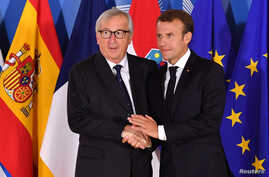 FILE - European Commission President Jean-Claude Juncker, left, shakes hands with French President Emmanuel Macron during an informal EU summit on migration at EU headquarters in Brussels, Belgium, June 24, 2018.