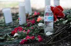 A bottle of water, flowers, candles, and stuffed animals help form a makeshift memorial in the parking lot of a Walmart store near the site where authorities discovered a tractor-trailer packed with immigrants in San Antonio, July 24, 2017.