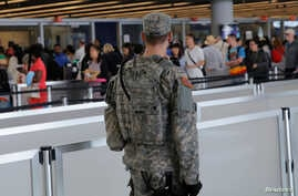 A U.S. Army Specialist monitors the security line at John F. Kennedy international Airport in the Queens borough of New York, June 29, 2016.