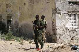 Government troops patrol a neighborhood destroyed by years of fighting in Mogadishu, January 10, 2008