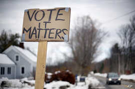 A handmade sign stuck in a snowbank on a rural road urges citizens to vote, Tuesday, Nov. 4, 2014, in Searsmont, Maine.
