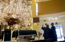 President Barack Obama learns about the Shrine of Our Lady of Charity from Father Juan Rumin Dominguez during an unannounced stop at the Miami church, May 28, 2015.