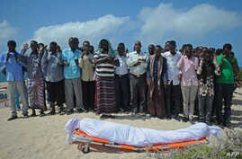 FILE -Relatives and fellow journalists pray as they stand next to the body of Somali journalist Abdulaziz Ali Haji during his funeral , Sept. 28, 2016, in Mogadishu.