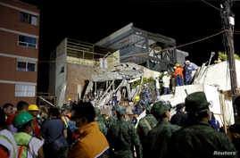 Rescue workers search through rubble during a floodlit search for students at Enrique Rebsamen school in Mexico City, Mexico, Sept. 20, 2017.