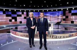 Candidates for the 2017 presidential election, Emmanuel Macron (R) and Marine Le Pen pose prior to the start of a live prime-time debate in the studios of French television station France 2, and French private station TF1 in La Plaine-Saint-Denis, ne
