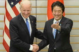 U.S. Vice President Joe Biden, left, is welcomed by Japanese Prime Minister Shinzo Abe prior to their talks at Abe's official residence in Tokyo, Dec. 3, 2013.