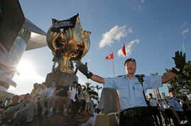 A policeman tries to stop members of the Demosisto political party and other pro-democracy activists from climbing a giant flower statue given to Hong Kong from Beijing in 1997 in Golden Bauhinia Square, Hong Kong, June 28, 2017.