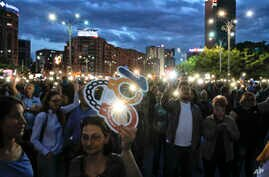 People flash the lights of their mobile phones during a protest outside the government headquarters in Bucharest, Romania, May 12, 2018. Thousands gathered to demonstrate against a judicial overhaul they say will make it harder to prosecute senior of