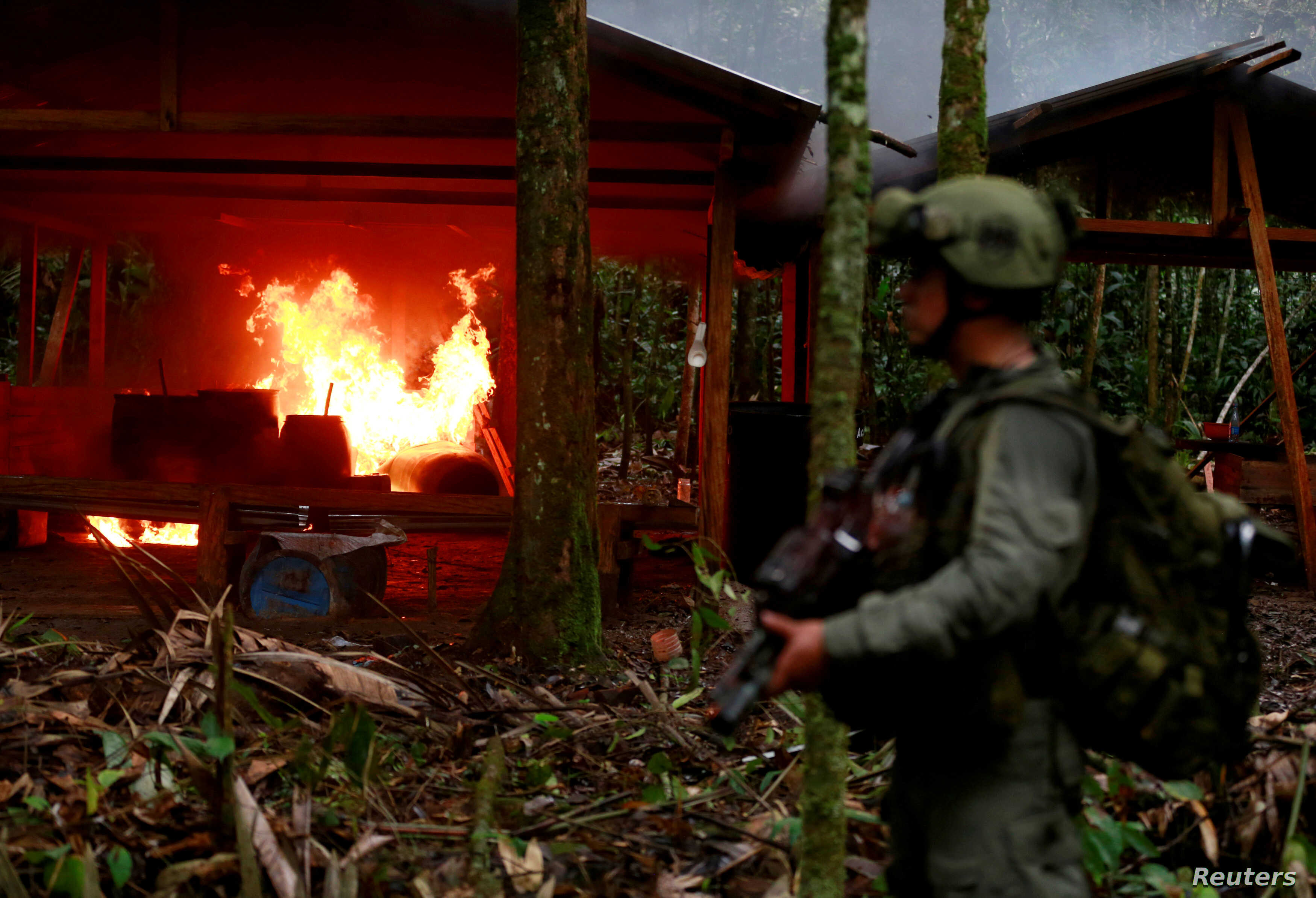A Colombian anti-narcotics policeman stands guard after burning a cocaine lab, which police said belongs to criminal gangs, in a rural area of Colombia, August 2, 2016. Colombia, one of the world's top cocaine producers, sold $2 billion in illegal d