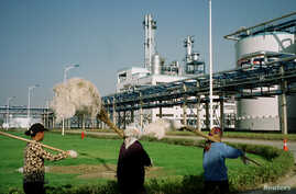 FILE - Workers walk past Jilin Fuel, one of the world's largest fuel ethanol plants, near the provincial capital Changchun of China's northeast Jilin province, early September 2003.