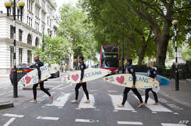 Climate change campaigners in wetsuits holding surfboards cross the road by the Houses of Parliament in London on June 17, 2015, ahead of a mass lobby to urge members of parliament to back strong action on climate change. AFP PHOTO / JUSTIN TALLIS