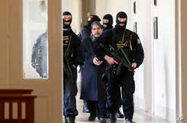 Policemen escort Salih Muslim, former co-chair of the Democratic Union Party, or PYD, to a court room for a custody hearing in Prague, Czech Republic, Tuesday, Feb. 27, 2018.
