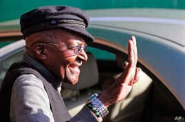 South African Anglican Archbishop Emeritus Desmond Tutu, center, waves after voting during municipal elections in Cape Town, South Africa, Wednesday, Aug. 3, 2016.