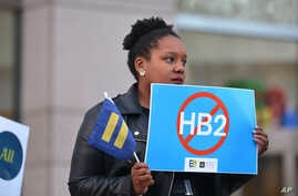 Cassandra Thomas of Human Rights Campaign holds a sign advocating the repeal of HB2 Dec. 7, 2016, in Charlotte, NC.