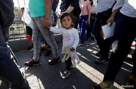 Migrant families from Mexico, fleeing from violence, enter the United States to meet officers of the U.S. Customs and Border Protection to apply for asylum at Paso del Norte international border crossing bridge in Ciudad Juarez, June 20, 2018.