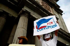 "A masked man holds up a sign that reads ""FCN Corruption,"" referring to the ruling party, Frente Convergencia Nacional, as he and others protest Guatemala's President Jimmy Morales at Constitution square in Guatemala City, April 21, 2018."