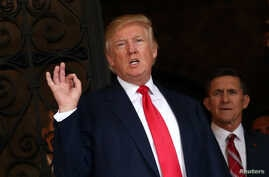 FILE - President-elect Donald Trump talks to members of the media as retired U.S. Army Lieutenant General Michael Flynn stands next to him at Mar-a-Lago estate in Palm Beach, Florida.